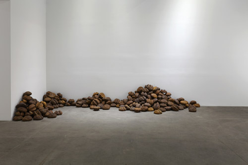 An installation consisting of hundreds of loaves of bread cast in iron