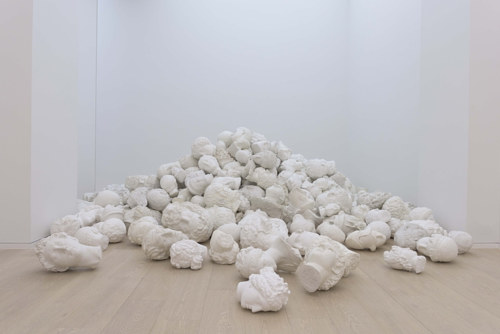An installation consisting of a number of plaster busts piled on the floor