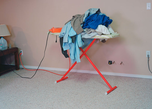 A photo of  an ironing board laden with clothes