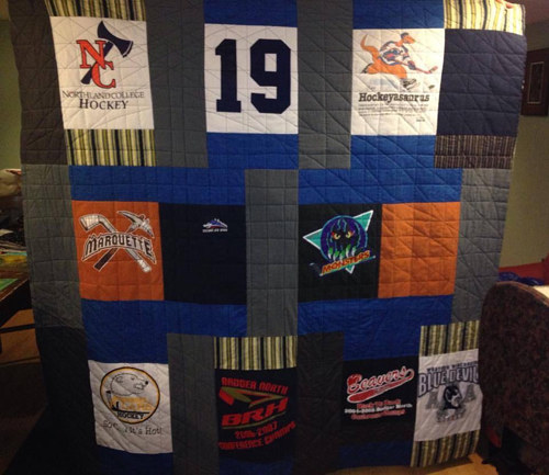 A quilt made with various sports-related t-shirts