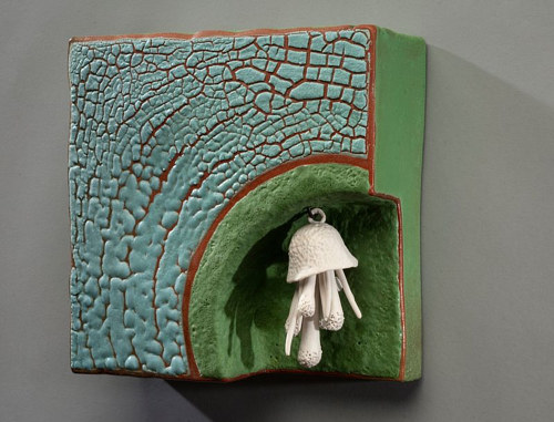 A wall sculpture consisting of a coloured panel with a small ceramic mushroom hanging from it
