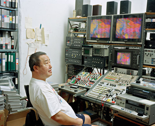 A photo of Nail June Paik working in his video editing studio
