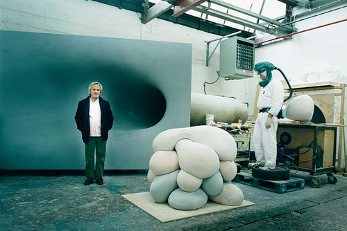 A photo of Anish Kapoor standing in his studio with an assistant