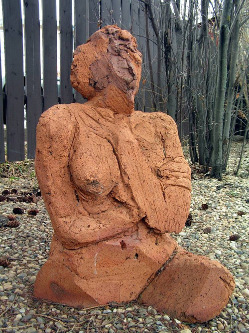 An unfired clay sculpture of a nude woman from the hips up