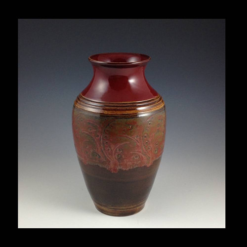 A tall vase with an earthy red glaze