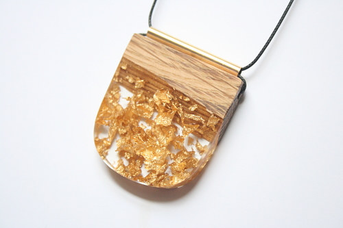 A handmade pendant made from wood and resin with gold flakes