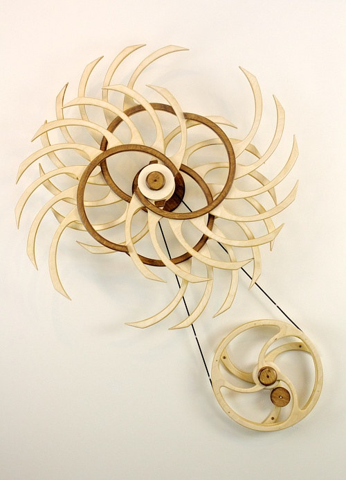 A kinetic wood wall sculpture that spins through its own momentum