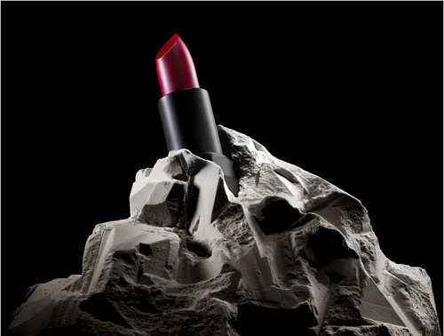 A photo of a tube of lipstick embedded in a lump of rock