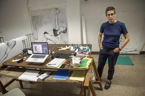 A photo of Alison Bechdel at work in her studio