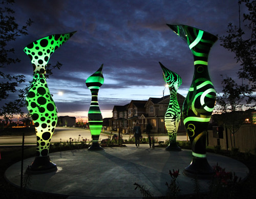 An outdoor sculpture with several monolithic structures lit with coloured LEDs