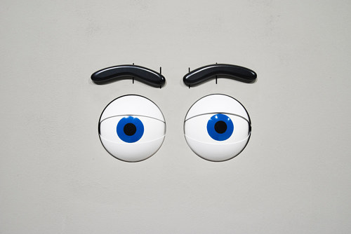 A set of animatronic eyes set into the wall of a gallery