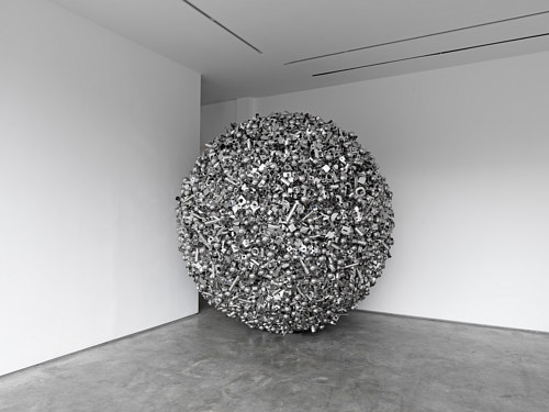 A sculpture consisting of a large ball of shiny objects