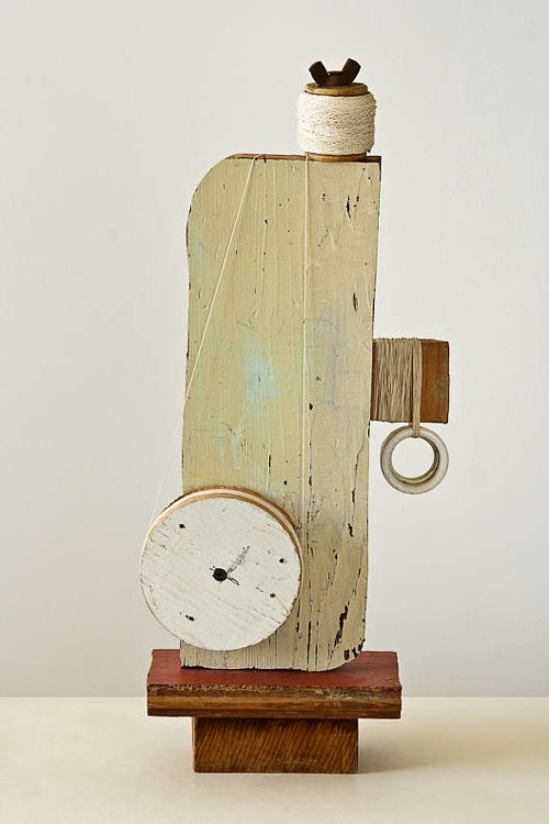 An assemblage artwork composed mainly of white wood and thread