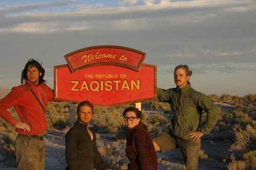 A photo of four artists in front of the Zaqistan sign