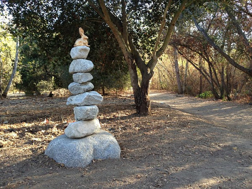 A temporary sculptural installation with a small rabbit sculpted on top of a stack of rocks