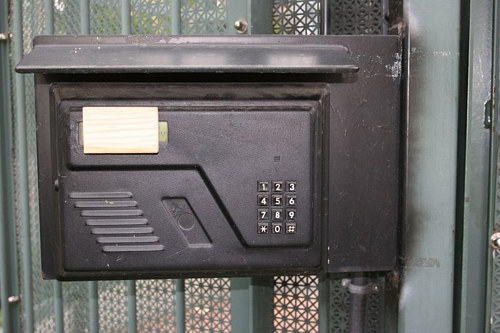 A photo of a small wood block over the display screen of an apartment buzzer panel