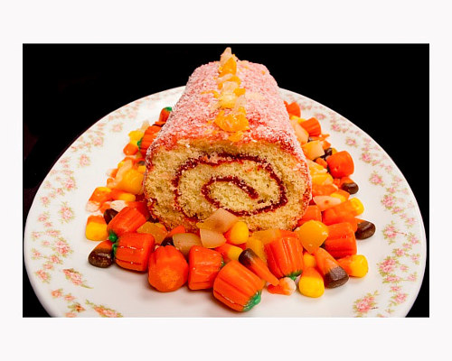 A photograph of a packaged cake surrounded by Halloween candies