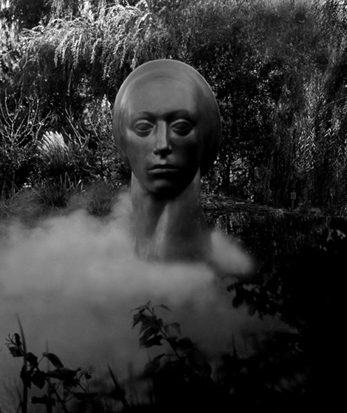 A black and white photograph of a statue in smoke
