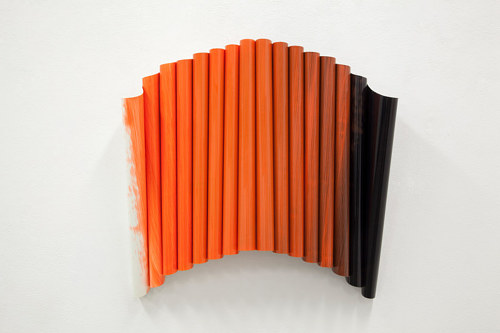 A painting in orange on rolled-up acetate sheets