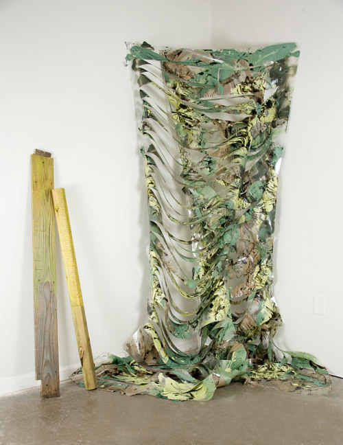 An installation featuring a sheet of torn camoflauge