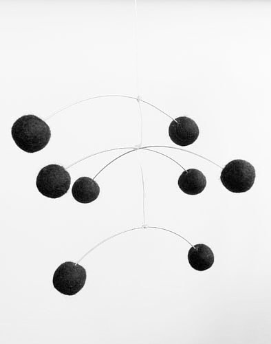 A mobile made with black spheres hanging on the end of silver wire