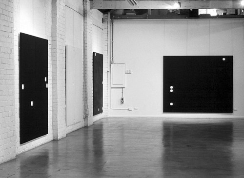 An installation view of three white-on-black paintings