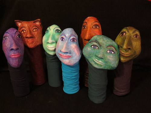 An image of a collection of papier mache bottle sleeves with faces