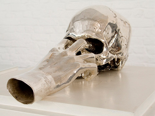 A cast silver sculpture of a hand with its fingers in a skull