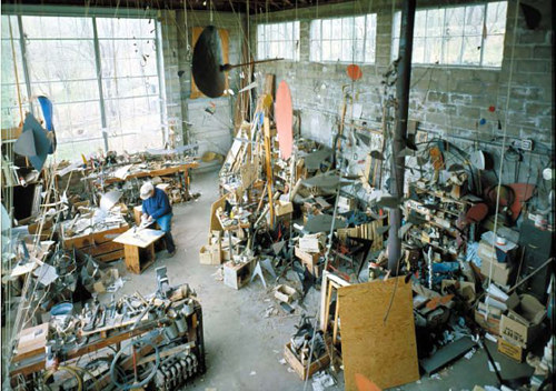 A photo of Alexander Calder working in his studio in the 1960's