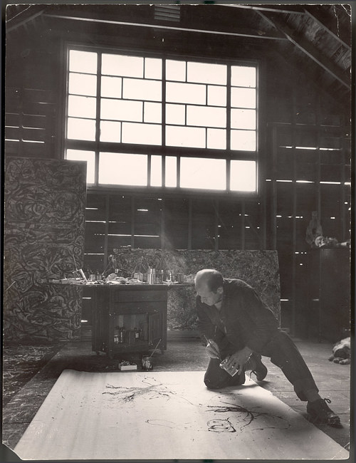 A photo of Jackson Pollock creating a painting in his studio