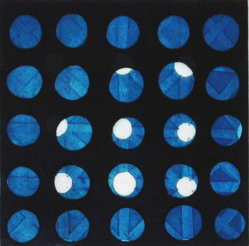 An etching made with a grid of circles in deep blue colours