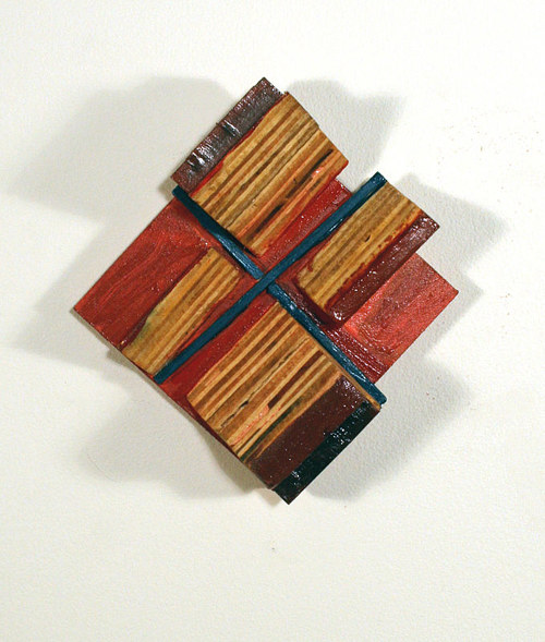 A small painted assemblage made from uneven pieces of wood