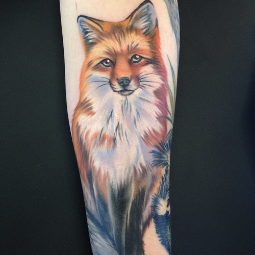 A forearm tattoo of a realistic fox