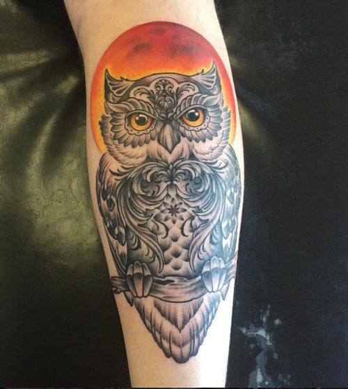 A tattoo of an owl in front of a red moon