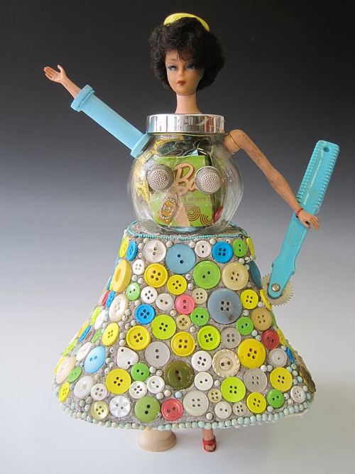 A sculpture of a teapot with the head of a Barbie doll on top