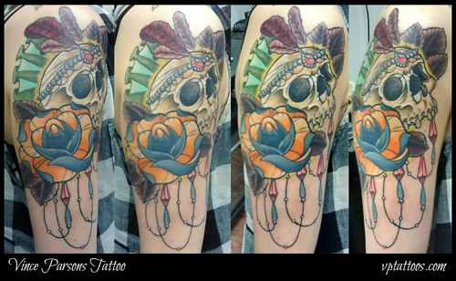 An arm tattoo of a skull with a flower