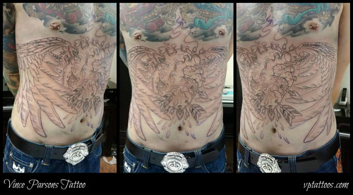 A front torso tattoo of a heart with wings in lineart