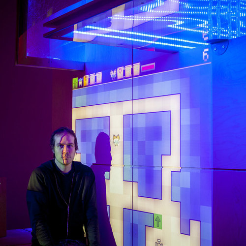 A photo of game designer Jason Rohrer in front of his exhibition at the Davis Museum