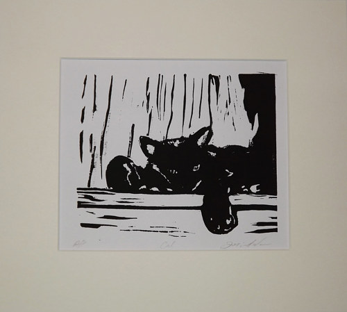 A black and white lino print of a reclining cat