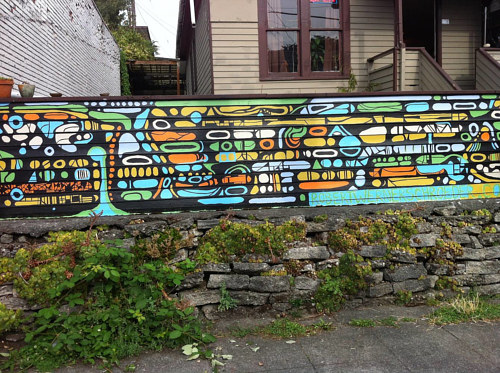 An outdoor mural on a retaining wall