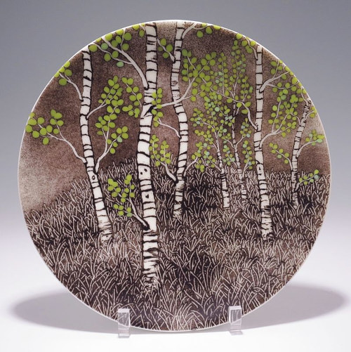 A glassware plate with a stylized forest painted on it
