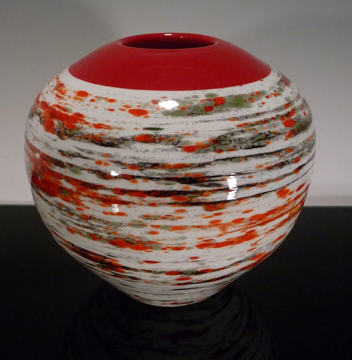 An earthenware vessel with a red and white abstract pattern