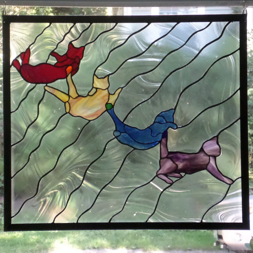 A stained glass panel depicting a cat landing on its feet