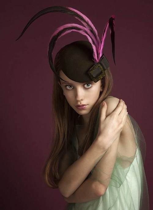 A photo of a model wearing a feathered cocktail hat