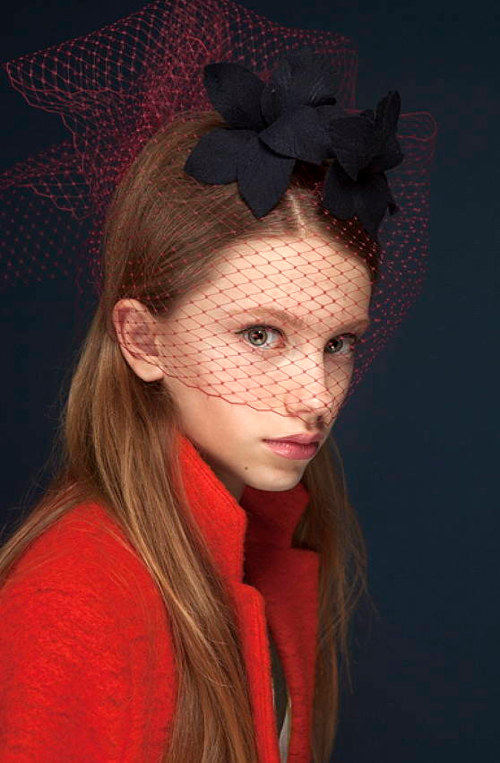A photo of a model wearing a navy orchid shaped hat with a red veil