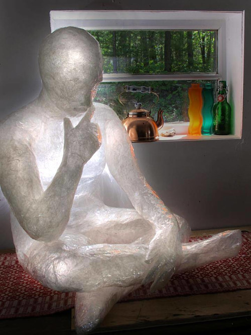A photo of a plastic sculpture of a sitting person