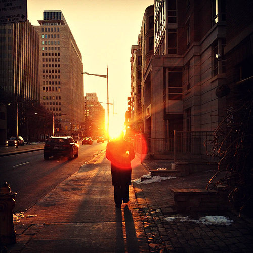 Photo of a man walking into the sunset