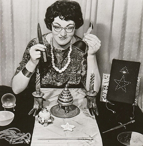 A photograph of Doreen Valiente holding up some pagan spiritual objects