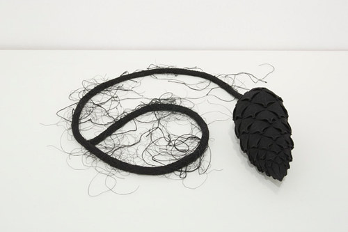 A linen and thread sculpture of a pine cone with a tail