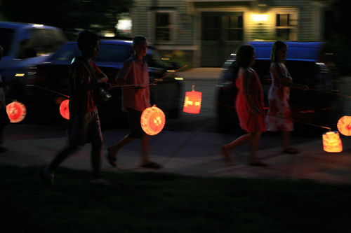 A photograph of several children carrying lanterns at night